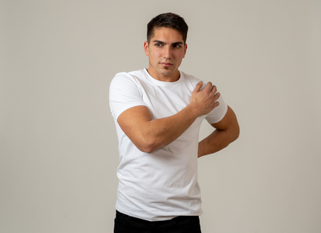Young muscular fitness man touching and grabbing his lower back suffering strong pain isolated on neutral background. In sport injury Incorrect posture problems and body health care.