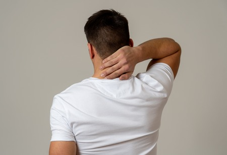 Young muscular fitness man touching and grabbing his neck and upper back suffering cervical pain isolated on neutral background. In sport injury Incorrect posture problems and body health care.