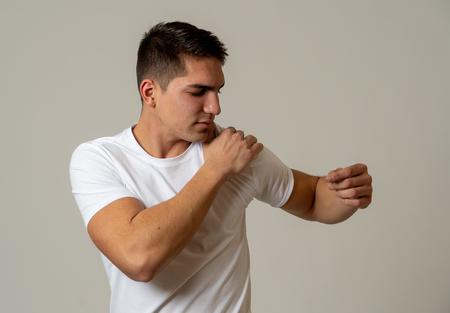 Junger muskulöser Fitnessmann, der seine Schulter berührt und ergreift und starke Schmerzen erleidet. Auf neutralem Hintergrund isoliert. Bei Sportverletzungen Falsche Haltungsprobleme und Körpergesundheitspflege.