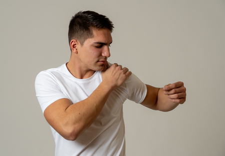 Young muscular fitness man touching and grabbing his shoulder suffering strong pain. Isolated on neutral background. In sport injury Incorrect posture problems and body health care. Standard-Bild