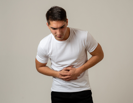 Young muscular fitness man holding his stomach suffering strong abdominal pain. Isolated on neutral background. In stomachache, digestive problems and health care issues. Zdjęcie Seryjne