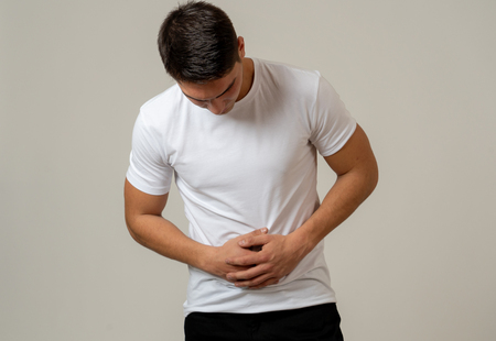 Young muscular fitness man holding his stomach suffering strong abdominal pain. Isolated on neutral background. In stomachache, digestive problems and health care issues.