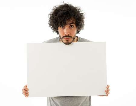 Funny and good looking millennial man showing and pointing at blank board with copy space for advertisement text. Looking happy surprised and shocked at great ad. In marketing concept.