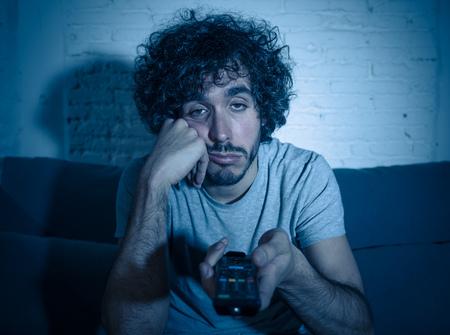 別の映画や夜遅くにショーのためにテレビリモコンザッピングを使用してソファの上の若い退屈な男。無関心で眠れないように見えます。エンターテイメントでは、人々の不眠症と座りっぱなしのライフスタイルの概念。