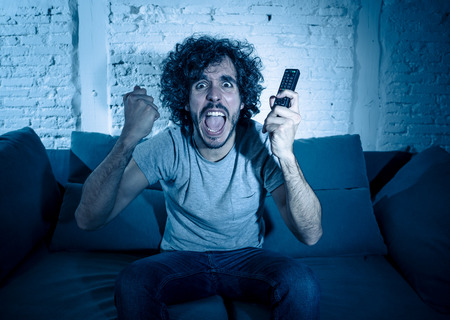 Lifestyle portrait of tv show fan man watching excited favorite series movie or soccer football game in online TV late at night. In people streaming content addiction and entertainment concept.