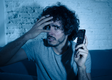 Lifestyle portrait of young man feeling scared and shocked making fear, anxiety gestures while watching television holding remote control. In horror and violence on TV and internet and mass media.
