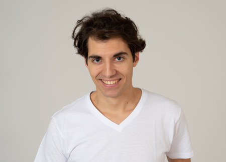 Close up portrait of happy young caucasian latin man wearing white T-shirt. Smiling feeling satisfied and confident. With copy space. People, positive human facial expressions and emotions concept.