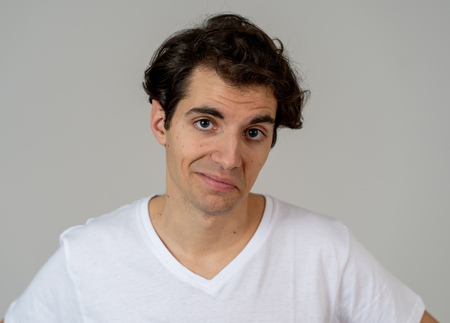 Portrait of young happy man with funny hilarious faces having fun. Millennial male making silly amusing gestures isolated against neutral background. In People human emotions and facial expressions.