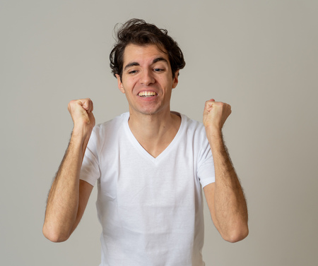 Portrait of very excites and shocked young man celebrating winning the lottery or having great success with surprised and happy gestures. In People, Facial Expression and Human Emotions. Studio shot. Banco de Imagens