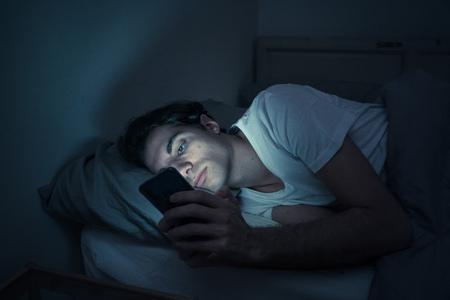 Uomo dipendente che chatta e naviga su Internet con uno smartphone a tarda notte a letto. Annoiato, insonne e stanco in una stanza buia con una luce lunatica. Nell'insonnia e nel concetto di dipendenza da dispositivi mobili.