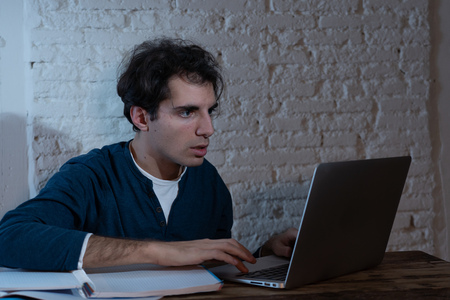 Close up portrait in moody light of happy casual attractive man working and studying on laptop sitting on desk at night. In working from home, online learning and final exams concept. Stock Photo
