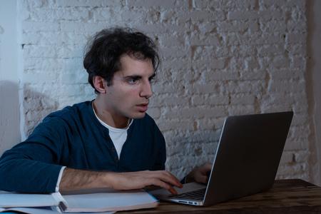 Close-up portret in humeurig licht van gelukkig casual aantrekkelijke man werken en studeren op laptop zittend op het bureau 's nachts. In thuiswerken, online leren en eindexamenconcept. Stockfoto