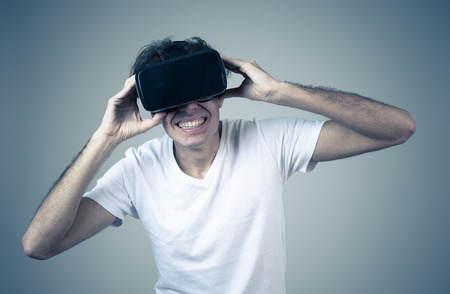 VR experience. Amazed and excited man using 360 VR headset goggles, feeling excited about simulation, making gestures having fun interacting with new virtual world. In Innovation and new technology. Stock Photo
