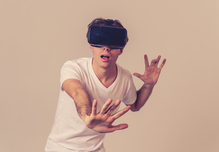 Young man using virtual reality goggles feeling excited and shock exploring virtual world making scared gestures having a scary VR adventure. Innovation New technology and Virtual Augmented Reality.