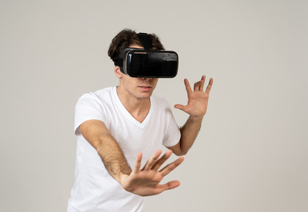 Amazed funny man using VR headset glasses touching and interacting with virtual reality world , feeling excited exploring and having fun in 360 VR simulation. Innovation and new technology concept.