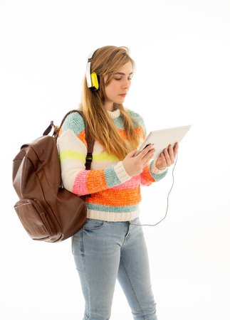 Portrait of happy young teenager student woman in headphones using tablet watching a video tutorial online curse or listening to music. Isolated white background. In technology and student lifestyle.