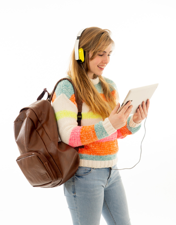 Portrait of happy young teenager student woman in headphones using tablet watching a video tutorial online curse or listening to music. Isolated white background. In technology and student lifestyle. Stock Photo