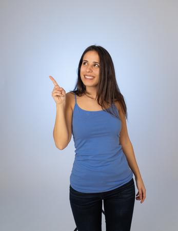 Bella giovane donna latina che punta il dito sullo spazio della copia che sembra allegra felice ed eccitata. Ragazza adolescente che mostra qualcosa di interessante isolato su sfondo vuoto per contenuti pubblicitari di testo.