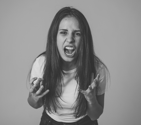 Close up of young attractive frustrated latin woman in stress with furious face. Looking mad and disappointed making angry gestures. In neutral background. In human facial expressions and emotions. Banque d'images