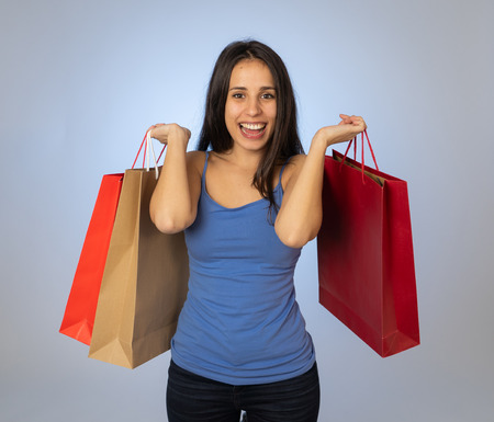 Happy latin young woman holding colorful bags happy and cheerful after a shopping day. Excited teenager with paper bags buying in new season sales. In fashion and and shopping addiction concept