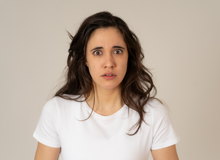Portrait of young latin woman feeling scared and shocked making fear, anxiety gestures. Looking terrified covering herself. Copy space. In negative human expressions and emotions concept.