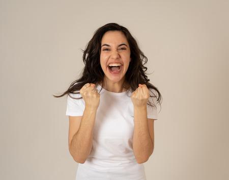 Giovane donna latina attraente che celebra il successo vincendo o si sente fortunata e gioiosa ballando facendo gesti di celebrazione con le braccia. Isolato su sfondo neutro Nelle espressioni e nelle emozioni delle persone. Archivio Fotografico