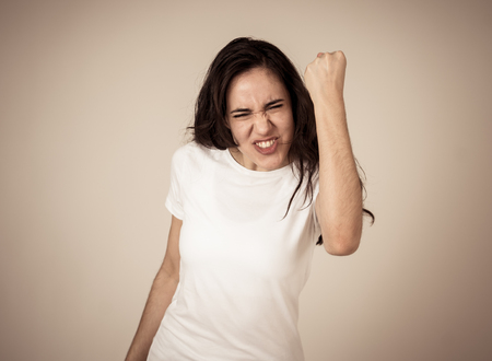 Young attractive latin woman celebrating success winning or feeling lucky and joyful dancing making celebration gestures with arms. Isolated on neutral background In People expressions and emotions.
