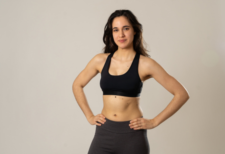 Beauty portrait of sport confident young latin woman wearing gym top looking sensual and fit. Studio shot of cheerful strong woman in sportswear looking healthy and sexy. In fitness Body care concept.