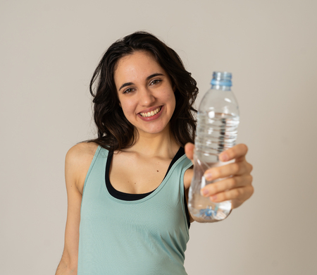 Portrait of beautiful fitness athlete Young latin Woman holding water bottle after work out exercising isolated on grey background in drinking water benefits to Health Fitness Stay hydrated concept. Banco de Imagens
