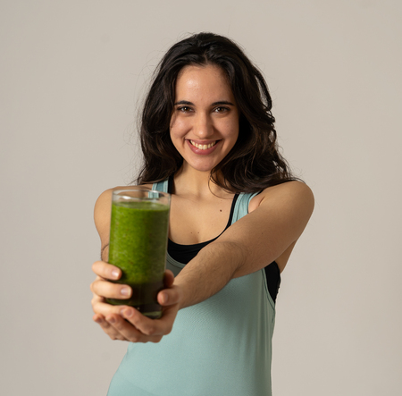 Fitness woman happy smiling holding glass of green vegetable smoothie after running or workout. Portrait isolated with copy space. Beauty Health Fitness Diet Nutrition and healthy Lifestyle concept.