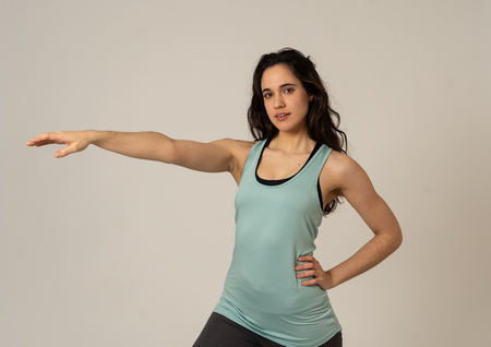 Cheerful latin strong woman in sportswear looking healthy and sexy. Portrait of fit young woman wearing gym top posing happy and funny in stretching and workout poses In Fitness and Body care concept.
