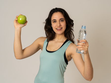 Happy fitness woman smiling holding an apple and water bottle feeling strong and healthy. In Healthy lifestyle, workout and nutrition concept. Portrait of latin model isolated on neutral background. 写真素材