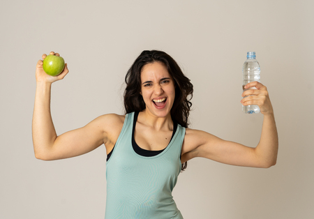 Happy fitness woman smiling holding an apple and water bottle feeling strong and healthy. In Healthy lifestyle, workout and nutrition concept. Portrait of latin model isolated on neutral background. Imagens