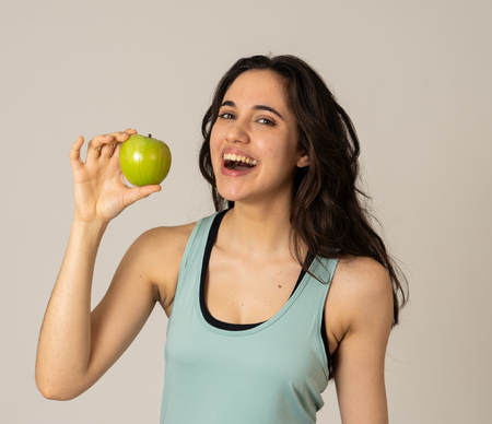 Beautiful fitness latin young woman showing green apple feeling strong, fit and happy having fruit after exercise training In Nutrition and Fitness, Healthy lifestyle, well being and body care.