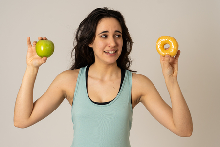 Beautiful young fit latin woman tempted having to make choice; apple and doughnut, healthy or unhealthy food. Fitness and nutrition healthy lifestyle and Diet concept. Studio shot with copy space.