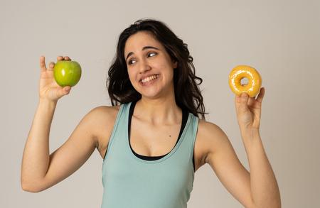 Belle jeune femme latine en forme tentée d'avoir à faire un choix ; pomme et beignet, aliments sains ou malsains. Fitness et nutrition mode de vie sain et concept de régime. Studio tourné avec espace de copie.