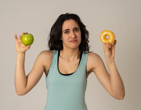Schöne junge passende lateinische Frau versucht, die Wahl treffen zu müssen; Apfel und Donut, gesundes oder ungesundes Essen. Fitness und Ernährung gesunder Lebensstil und Diätkonzept. Studioaufnahme mit Kopienraum. Standard-Bild