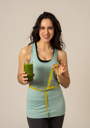 Fitness woman smiling happy with diet plan to loose weight; exercise and green vegetable smoothie healthy drink. In Beauty body care, Health Fitness Diet Nutrition and healthy Lifestyle concept.