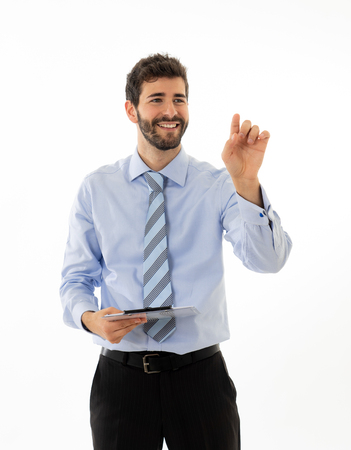 Young attractive businessman pointing at copy space as using a virtual screen. Smiling feeling confident and successful. In people business education, success and new technology at work concept.