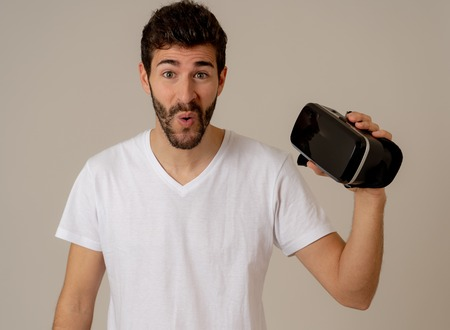 Virtual reality experience. Young caucasian bearded man happy to use VR goggles feeling excited about simulation and exploring virtual life. In New technology Virtual Augmented Reality concept.