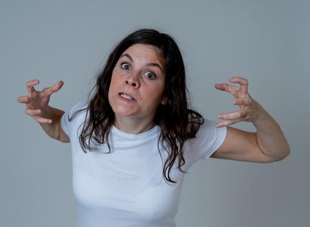 Expresiones faciales y emociones. Retrato de mujer caucásica atractiva joven con una cara enojada. Luciendo loco y loco gritando y haciendo gestos furiosos. Aislado sobre fondo neutro.