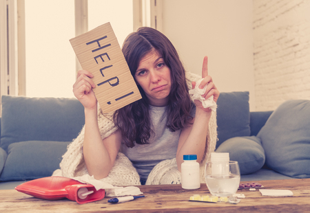 Health care. Sick attractive woman feeling unwell with flu headache sore nose high temperature asking for help holding a sign feeling fatigue and restless not being able to go to work. Stock Photo