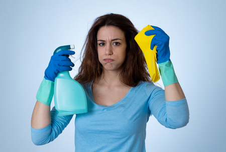 Angry and upset woman with cleaning spray and cloth cleaning feeling frustrated. The stain will not come out. In domestic duties and cleaning products advertising image isolated on blue background.