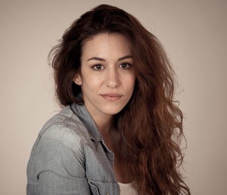 Retrato de joven bella mujer con cara feliz, hermosa sonrisa y pelo rojo largo y rizado de cerca. Posando en camisa de jeans y mirando a la cámara sonriendo. En concepto de modelado de moda Beauty Care.