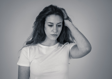 Portrait of young sad woman looking worried in emotional pain. Feeling sorrow and suffering from depression. Isolated in neutral background. In mental health and facial expressions and emotions.