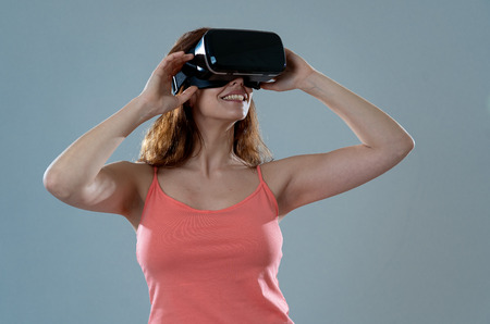 Erstaunte Frau, die Erfahrung mit VR-Headset-Brillen macht, sich für die Simulation begeistert, die virtuelle Realität erforscht und Gesten macht, die mit der neuen virtuellen Welt interagieren. Im neuen Technologiekonzept.