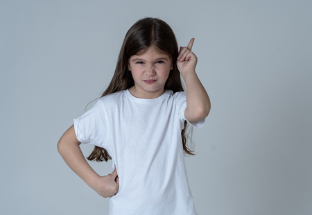 Close up portrait of a cute pretty child looking angry and disappointed pointing with finger against neutral background. In Children feelings and behavior and human emotions and expressions.