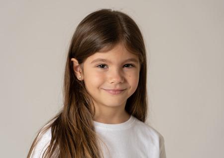 Linda niña feliz, segura, exitosa y orgullosa sonriendo a la cámara. Las emociones humanas positivas y las expresiones faciales, los niños y el concepto de educación. Foto de estudio con espacio de copia.
