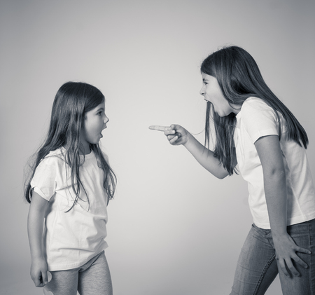 Portrait of siblings interacting having an argument. Older sister shouting and making furious gestures to her angry sad younger sister. Siblings bad relationship and children conflicts.