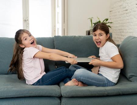 Chicas más jóvenes y mayores que luchan por una computadora portátil discutiendo sobre jugar en Internet. Retrato de estilo de vida de hermanas que no comparten computadora en relación entre hermanos y concepto de adicción a la tecnología.